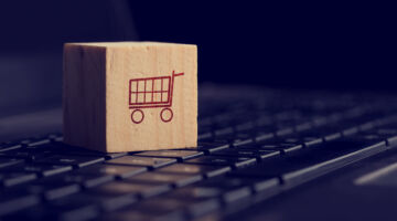 Online shopping and e-commerce background with a wooden cube showing a shopping cart icon resting on a computer keyboard viewed low angle over black with copyspace.